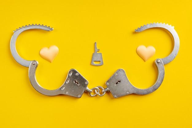 Menottes ouvertes sur fond jaune. sortie de prison, concept de liberté. emprisonnement, privation de liberté et appréhension des auteurs.