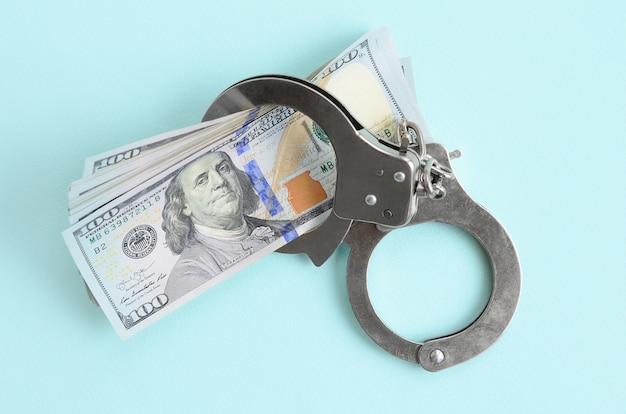 Des menottes de police en argent et des billets de cent dollars se trouvent sur un fond bleu clair