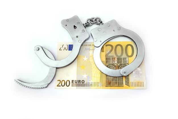 Menottes de police et billets de 200 euros sur fond blanc - concept de finance et de crime