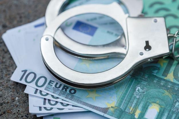 Des menottes se trouvent sur un paquet de cent euros. photo de haute qualité