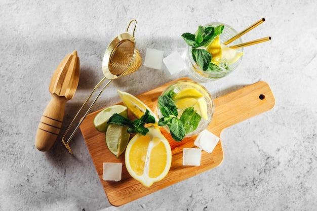 Menthe, citron vert, glace citrons et ustensiles de bar sur planche à découper en bois sur fond de marbre blanc vue de dessus