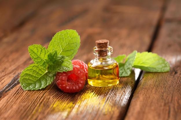 Menthe poivrée et huile de framboise sur une table en bois.