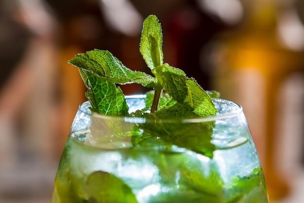 Menthe en verre avec boisson. feuilles vertes sur petite branche. boisson alcoolisée servie à la fête. cocktail hugo à l'eau minérale.