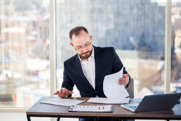 Mentor masculin adulte, réalisateur, homme d'affaires à lunettes et un costume étudiant des documents tout en étant assis à la table. notion de jour ouvrable