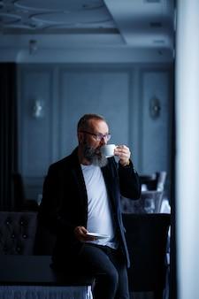 Un mentor, un réalisateur, un homme d'affaires portant des lunettes et un costume boit du café et se repose. notion de jour ouvrable