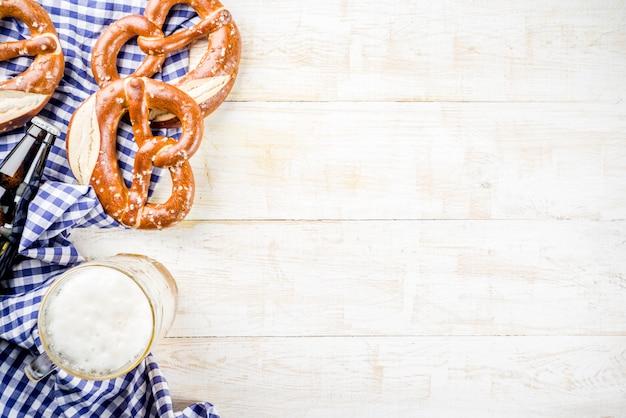 Menu alimentaire oktoberfest, bretzels bavarois avec une tasse de bière, fond en bois blanc