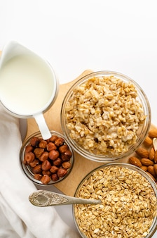 Menu diététique pour le petit déjeuner avec bol d'avoine aux noix et pot de lait sur une planche de bois