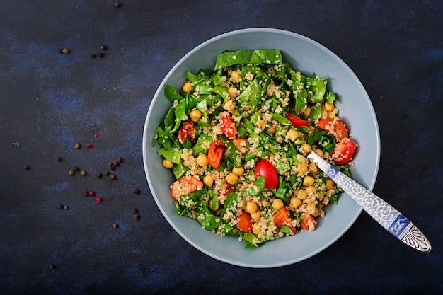 Menu diététique. salade végétalienne saine de légumes frais - tomates, pois chiches, épinards et quinoa dans un bol.
