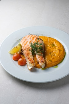 Menu du restaurant steak de truite servi avec purée de carottes et pommes de terre