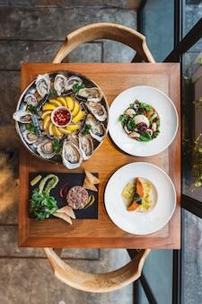 Menu fusion: huîtres fraîches, raviolis à la crème et saumon grillé