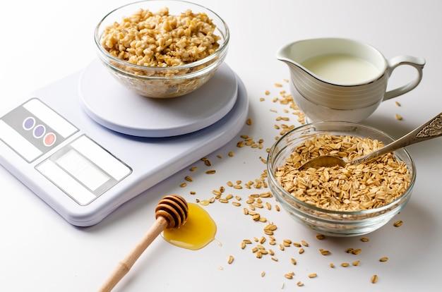 Menu nutritionnel approprié pour le petit-déjeuner avec bouillie de flocons d'avoine sur des balances de cuisine numériques, lait et miel