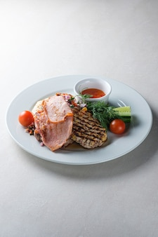 Menu pour le restaurant une assiette avec poitrine de porc poulet légumes et sauce