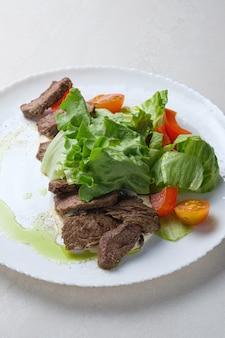 Menu pour le restaurant salade avec laitue de boeuf et tomates cerises et vinaigrette aux épices
