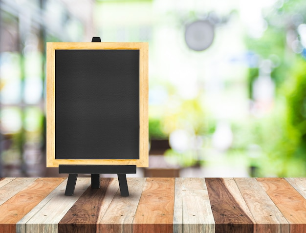Menu tableau noir avec chevalet sur la table en bois avec café flou