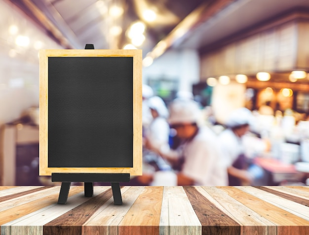 Menu tableau noir avec chevalet sur la table en bois avec cuisine ouverte flou