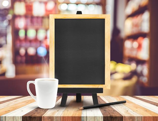 Menu tableau noir avec chevalet sur une table en bois avec une tasse de café et un crayon