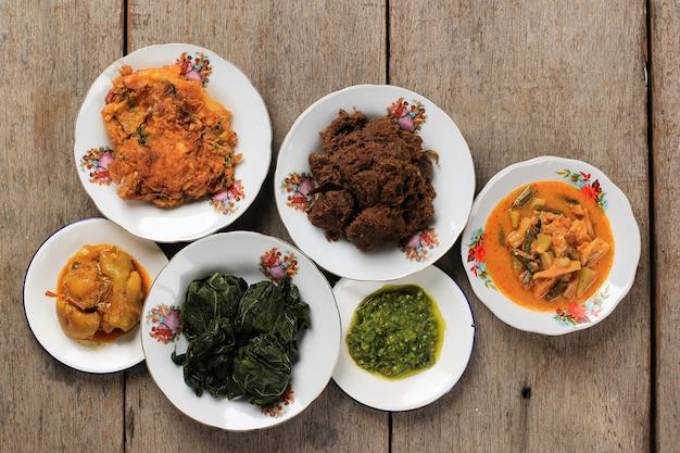 Menu varié du restaurant padang. maison masakan padang ou cuisine minang sur fond rustique. servi sur plaque émaillée, style maison nasi padang pour lebaran menu