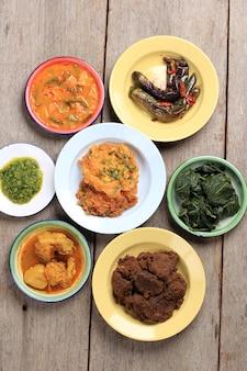 Menu varié du restaurant padang. maison masakan padang ou cuisine minang sur fond rustique. servi sur plaque émaillée, style maison nasi padang