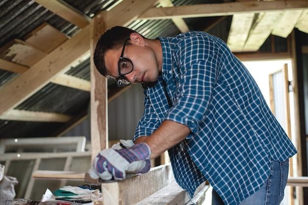 Menuiserie. charpentier rabote le bois en atelier. travail du bois, toiture, bricolage.
