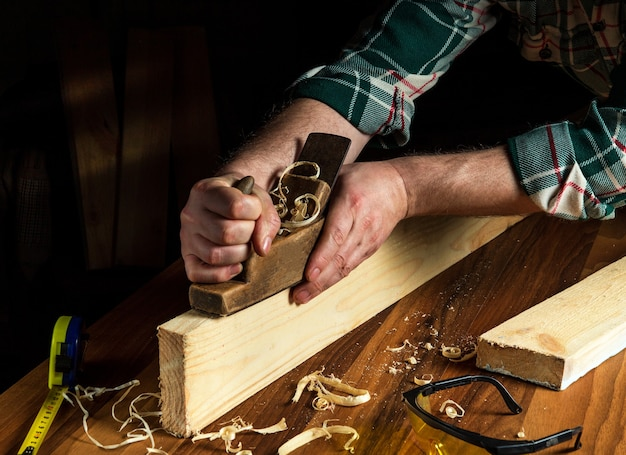 Menuisier à l'aide d'un rabot à main pour nettoyer une planche de bois. mains du maître gros plan au travail.