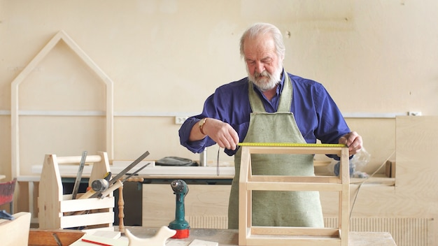 Menuisier aux cheveux gris travaille dans son atelier.