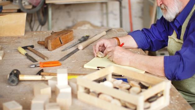 Menuisier barbu aux cheveux gris travaille avec des pièces en bois