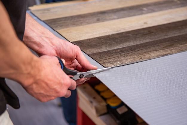 Menuisier faisant son travail dans l'atelier de menuiserie. un homme dans un atelier de menuiserie mesure et coupe le stratifié