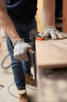 Menuisier homme en gants blancs pinces conseil en vice à l'atelier