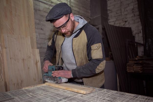 Menuisier mâle brutal polit une planche de bois avec une ponceuse dans son atelier