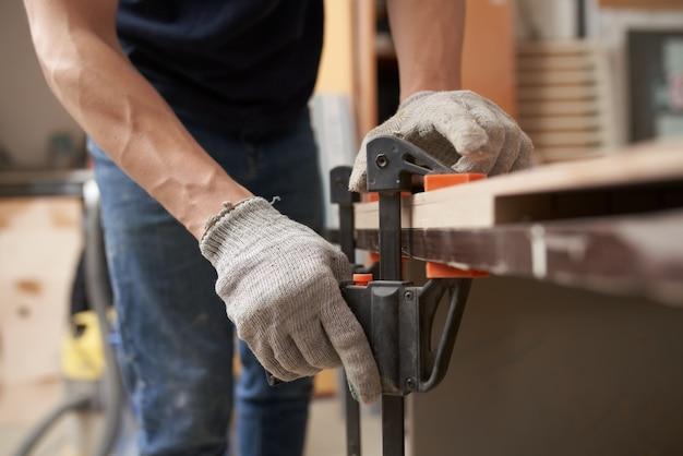 Menuisier mâle en gants pinces conseil en vice à l'atelier