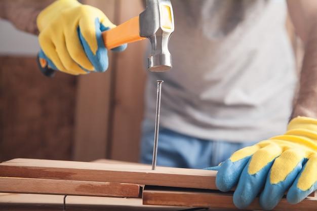 Menuisier avec marteau frappant un clou sur une planche en bois.