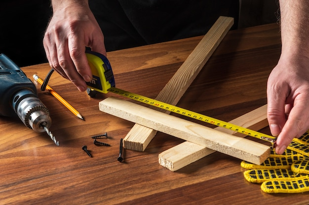 Le menuisier ou le menuisier utilise un ruban de construction pour mesurer la longueur d'un morceau de bois.