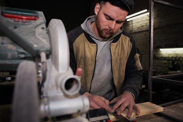 Menuisier mesure une planche de bois. photo en gros plan d'un travailleur en salopette