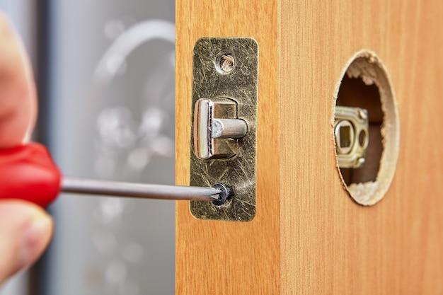 Un menuisier pousse la plaque frontale rectangulaire standard, glisse le loquet en place avec le montant de porte en biseau et le fixe avec deux vis courtes.
