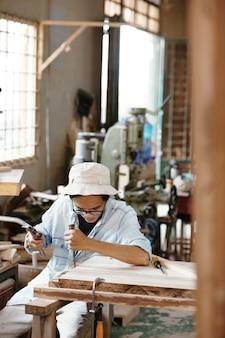 Menuisier professionnel avec ciseau et marteau découpant une planche de bois lors de la fabrication d'un meuble pour le client