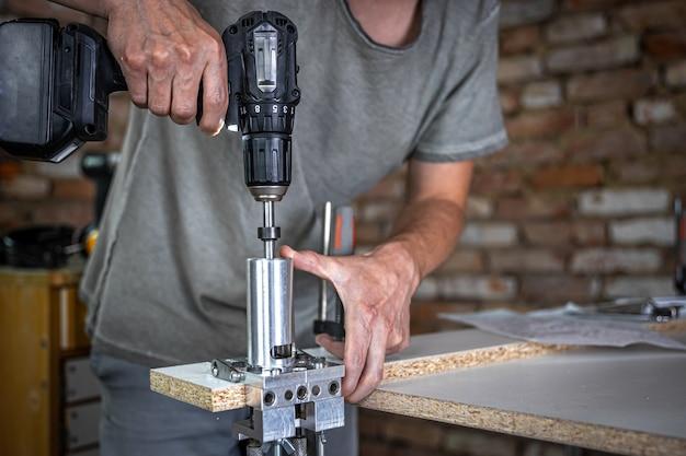 Menuisier professionnel travaillant avec du bois et des outils de construction dans la maison.