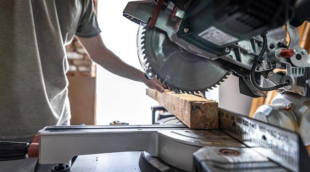 Un menuisier professionnel travaille avec une scie circulaire à onglets dans un atelier.
