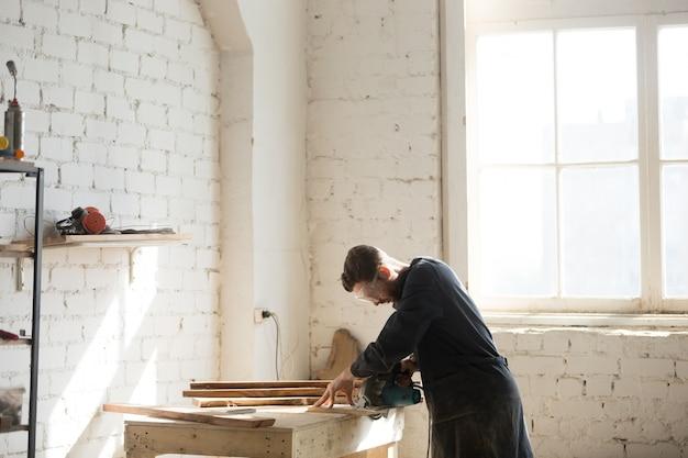 Menuisier professionnel utilisant scie à main électrique en atelier, vue de côté