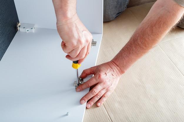 Le menuisier récupère les meubles à l'aide d'un tournevis à main. assemblage de meubles. déménagement, rénovation domiciliaire