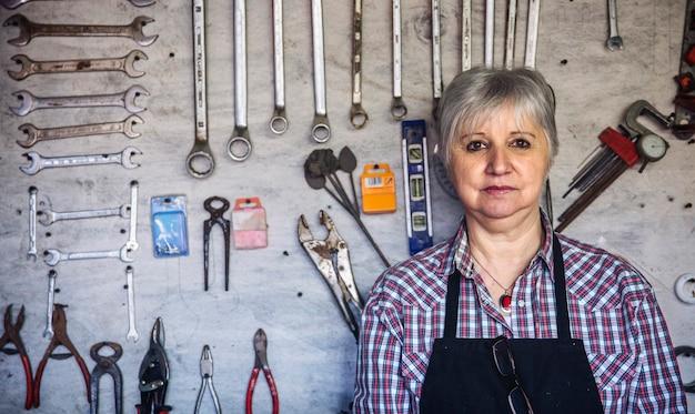 Menuisier senior posant les bras croisés dans son atelier