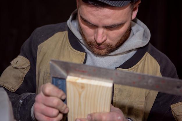 Un menuisier sérieux mesure la géométrie correcte de la planche avec un carré