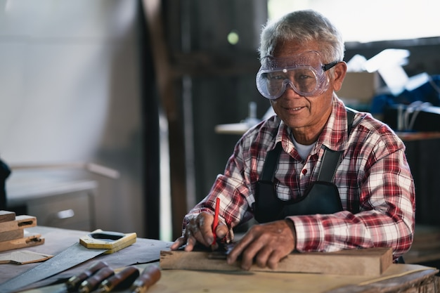 Menuisier travaillant sur le bois dans l'atelier de menuiserie. l'homme travaille dans un atelier de menuiserie