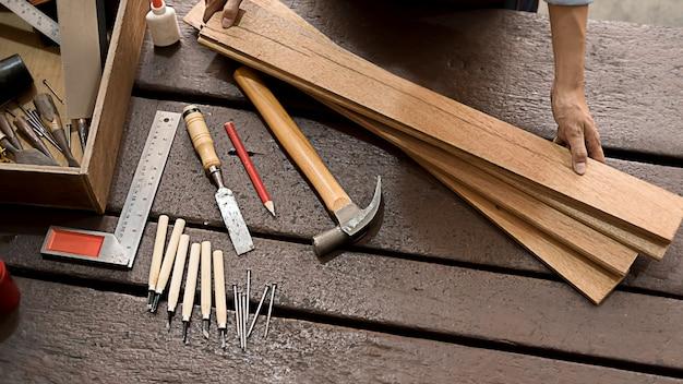 Menuisier travaillant avec du matériel sur une table en bois dans l'atelier de menuiserie. femme travaille dans un atelier de menuiserie.