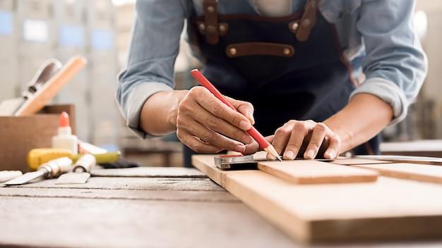Menuisier travaillant avec des équipements sur une table en bois dans un atelier de menuiserie.