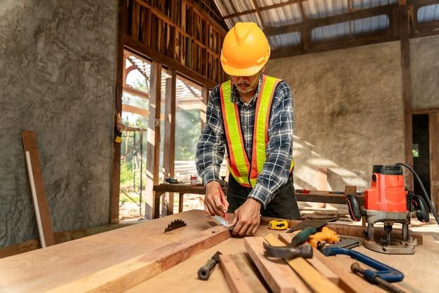 Un menuisier travaillant sur des machines à bois dans un atelier de menuiserie. le charpentier travaille sur le chantier de construction