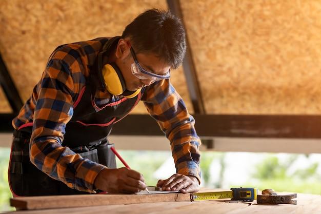Menuisier travaillant sur des machines à bois dans l'atelier de menuiserie. l'homme travaille dans un atelier de menuiserie en utilisant le premier concept de sécurité des écouteurs de protection.