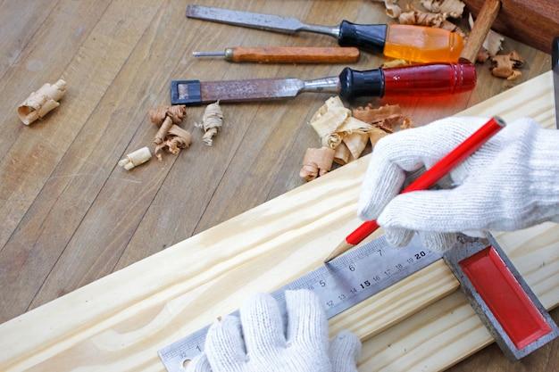Menuisier travaillant sur le travail du bois tenant une règle sur le banc de travail