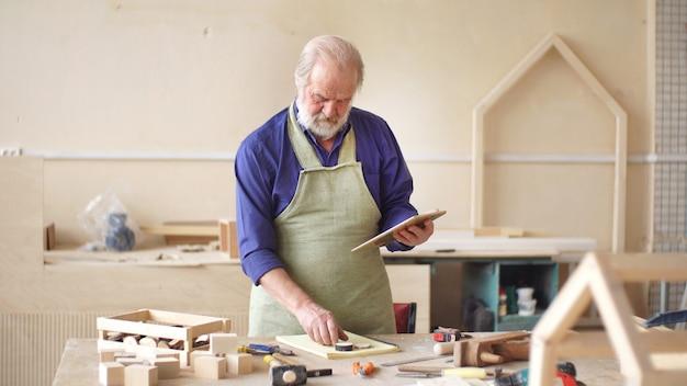 Menuisier travaille en atelier faisant un croquis de nichoir