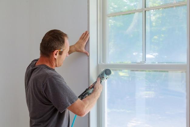 Menuisier utilisant un pistolet à clous pour mouler des fenêtres, encadrer des moulures,