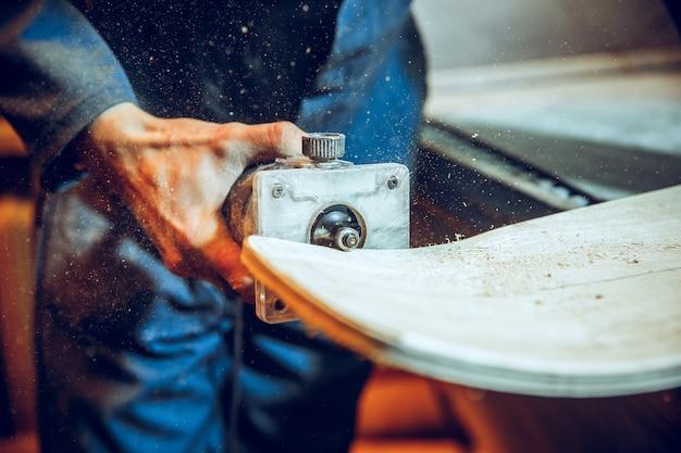 Menuisier utilisant une scie circulaire pour couper des planches en bois. détails de construction de travailleur masculin ou homme à tout faire avec des outils électriques